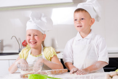 kids wearing a white chefs uniform smiling