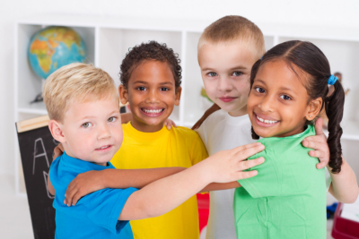 Four happy diverse preschool friends hugging in a circle in classroom