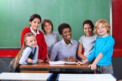 Portrait of happy African American female teacher and schoolchildren together at desk in classroom